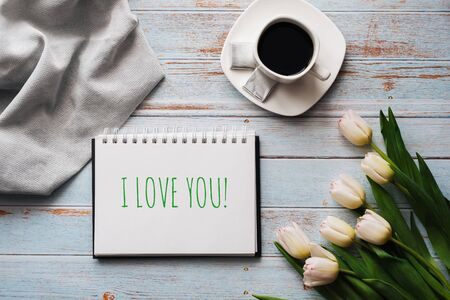 Greeting card with the inscription I Love You. Bouquet of white Tulip flowers with a Cup of coffee