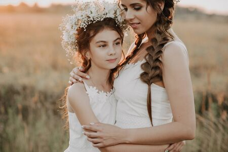 mom and daughter hugging together in white dresses with braids and floral wreaths in summer Foto de archivo