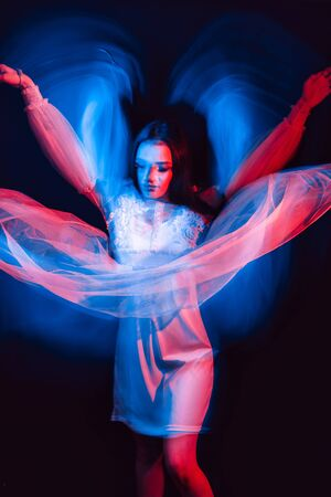 abstract portrait of a dancing girl in a dress with neon red and blue light