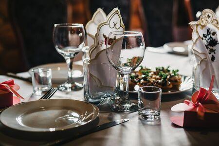 Satz leere Gläser und Teller mit Besteck auf einer weißen Tischdecke auf dem Tisch im Restaurant Standard-Bild