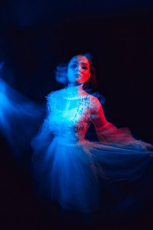 sad Ghost girl in white dress dancing on dark background