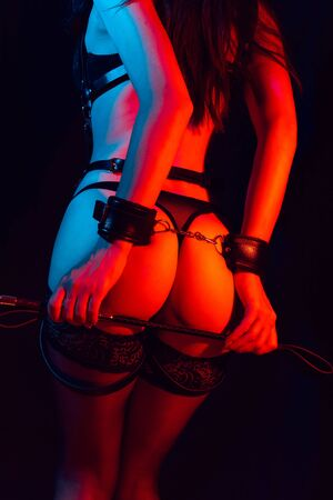 sexy ass slave girl with hands in leather handcuffs and whip