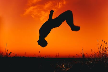 Male athlete jumps and does somersaults in nature in summer