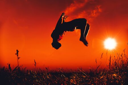 man jumps and does a back flip in the summer in nature Stock Photo