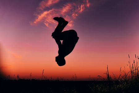 silhouette of a man doing a somersault in the summer in nature
