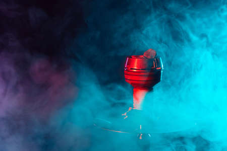 red hot shisha coals in a metal hookah bowl against a background of multicolored smoke