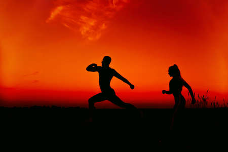silhouettes of a couple running in nature in summer at sunset against an orange sky