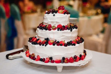 white wedding cake with strawberries, cherries, blueberries, black currants with three tiers