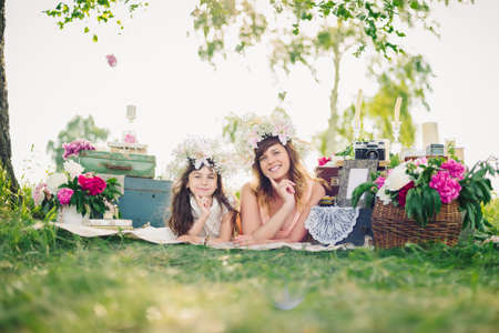 happy mother and daughter lying on a blanket outdoors on a Sunny summer