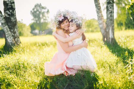 mom hugs her daughter sitting on the grass outdoors on a Sunny summer