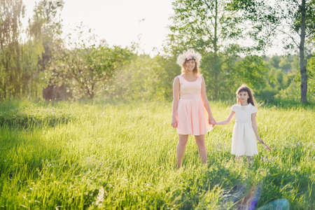 mom and daughter walking on the field in the summer Sunny day at sunset Stock fotó