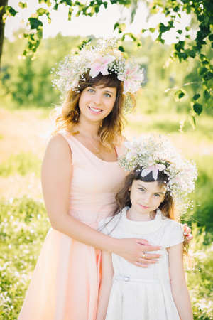 mom with an attractive smile hugging her daughter in the Park in the summer