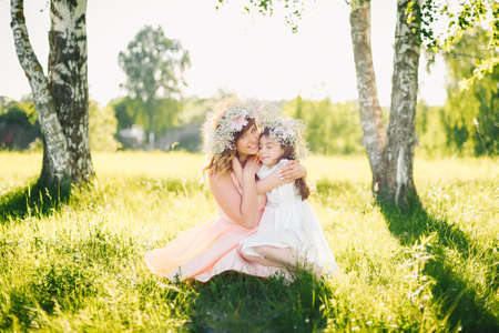 happy beautiful mother with a daughter of Caucasian appearance hugging in the meadow Stock fotó