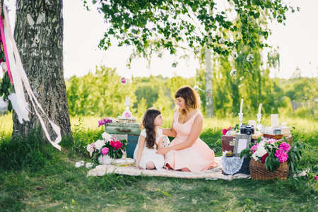 happy beautiful mother and daughter resting on a blanket in nature on a summer