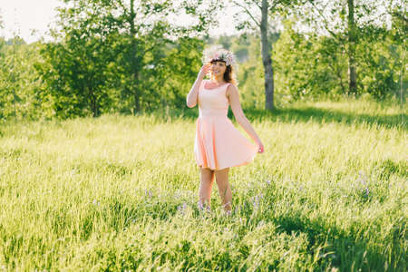 beautiful girl in a dress of Caucasian appearance with a wreath on her head on a meadow