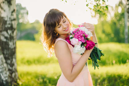 happy smiling girl with flower bouquet outdoors in summer Stock fotó