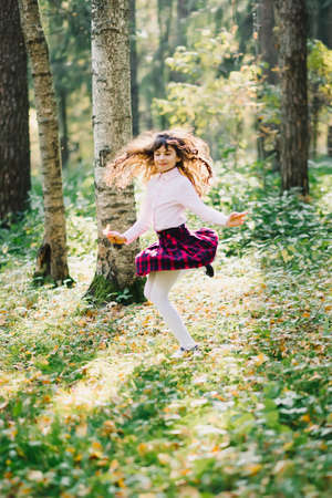 happy beautiful brunette girl is spinning and enjoying herself in the Park