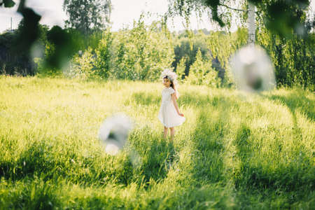 girl in a white dress with a wreath on her head on a meadow in nature