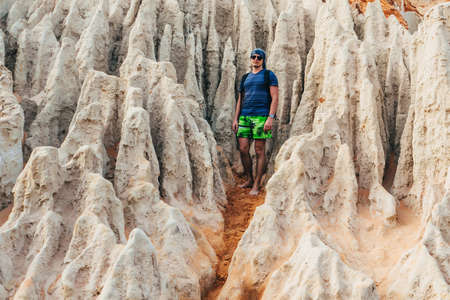 man tourist stands in the sandy rocks of the Fairy Steam in the Red Canyon in Vietnam
