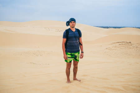 man tourist with a backpack and a bandana in the sandy desert Stock fotó