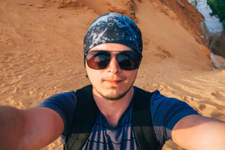 man Hiking makes a selfie on the camera face in sunglasses and a bandana