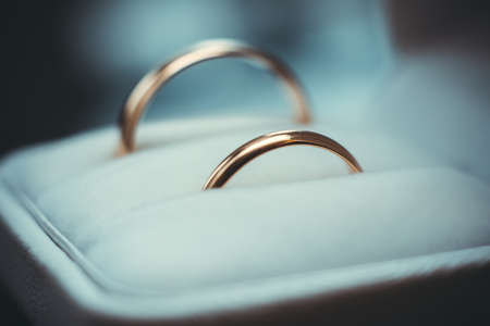 two gold wedding traditional rings lie in a white box