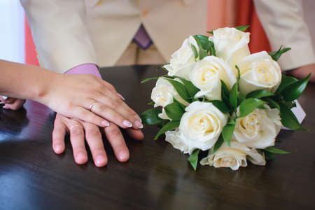 hands of the bride and groom with gold rings at the wedding
