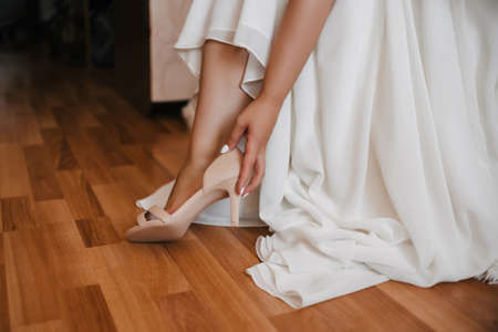 bride in a white dress wears a Shoe on the wedding day