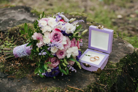 wedding rings in a box next to the bouquet