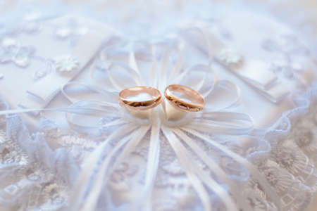 pair of gold wedding traditional rings on a white lace cushion Stock fotó