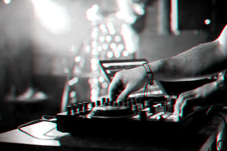 hands DJ mixing and playing music on a professional controller mixer