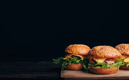 three homemade hamburgers with meat, cheese, lettuce, tomato on a wooden Board on a table on a black background