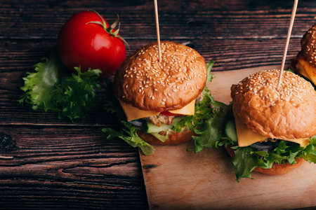 two hamburgers with meat, cheese, salad, tomatoes on a Board Stock fotó