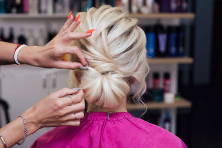 hairdresser makes his own hands hairstyle a bun on the head of a blonde girl