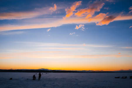 silhouettes of fishermen on winter fishing on the ice of the river