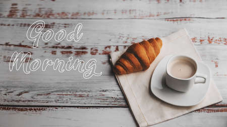 Greeting card with the inscription Good morning. A Cup of coffee and a croissant Banco de Imagens
