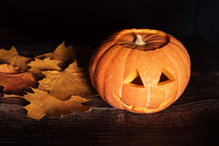festive Jack-o  - lantern pumpkin for Halloween with maple leaves Banco de Imagens