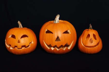 pumpkins with carved faces for Halloween celebration on black background Banco de Imagens