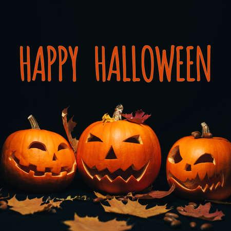 Three Jack-o  - lantern pumpkins on a black background with maple leaves