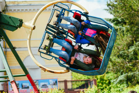 VICHUGA, RUSSIA - JUNE 24, 2017: Two girls ride a carousel in the Park on the Day of Vichuga Editorial