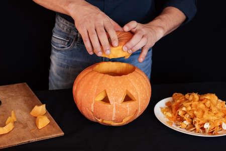 Halloween pumpkin. Man hands prepares traditional decoration for the celebration