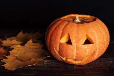 pumpkin for Halloween celebration with autumn orange maple leaves