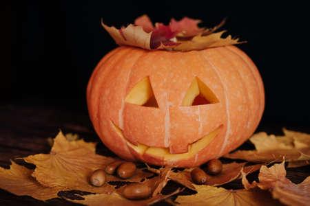 Jacks Halloween orange pumpkin with maple leaves and acorns on a dark background Banco de Imagens