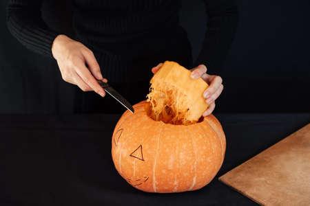 Halloween. Girls hands with a knife cutting orange pumpkin for making Jacks lantern