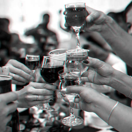 hands of a group of friends clinking glasses of wine and toasting Stock Photo