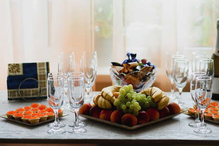 empty champagne glasses and fruit on the table Фото со стока