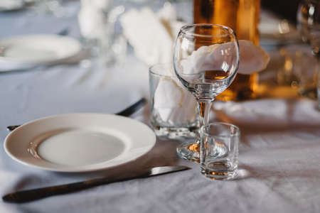 set of empty glasses and plates with Cutlery on a white tablecloth on the table in the restaurant Фото со стока