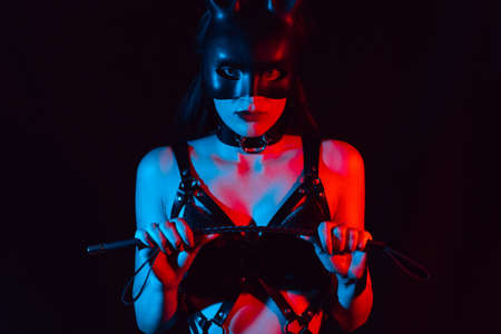 girl is a sexy mistress in a leather belt with a BDSM whip