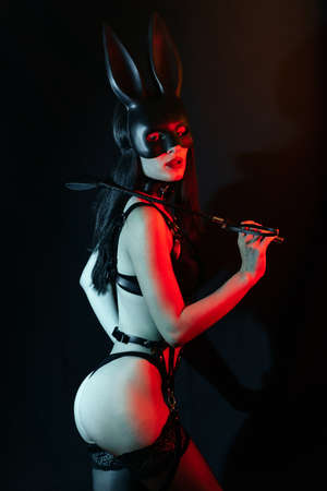 mistress girl with sexy ass in harness in Bunny mask with leather whip
