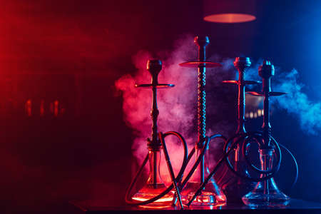 hookahs with shisha coals in bowls against a background of smoke with neon lighting